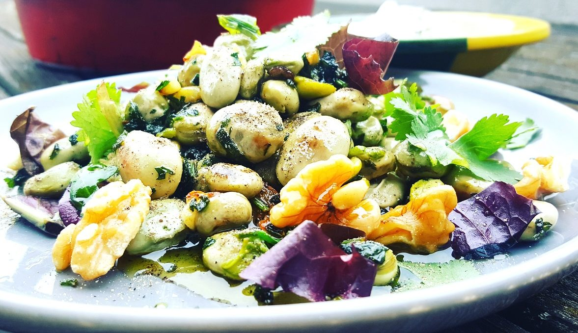 A plate full of gnocchi with fresh pesto, herbs, and walnut halves drizzled with a culinary oil.