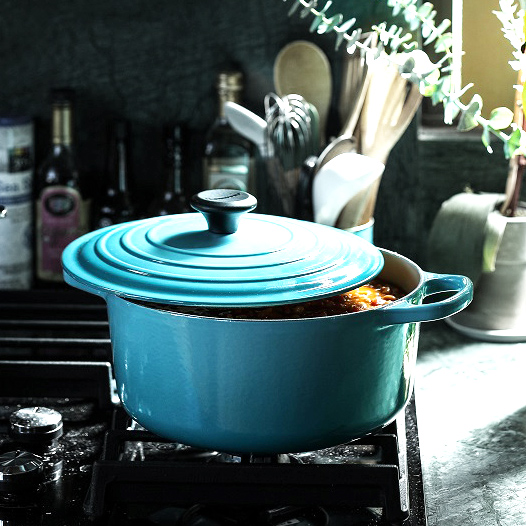 Blue ceramic coated cocette on the stovetop and full of stew