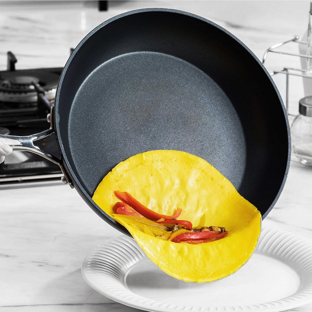 Non-stick frying pan sliding an open face omelette onto a place