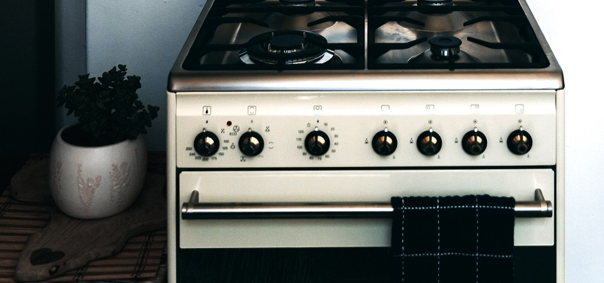 A clean and tidy gas stove with glistening silver knobs and a fresh kitchen towel.