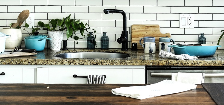 View of a clean kitchen sink and granite countertop, one of the key spots where harmful bacteria may lurk.