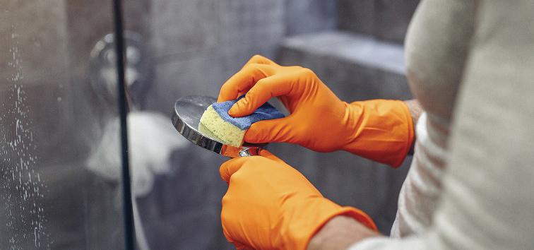 Two gloved hands scrubbing a bathroom shower head with DIY bathroom shower, bathtub, sink and toilet scrub.