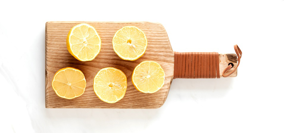 A wooden cutting board with lemon halves on top. Ready to be cleaned.