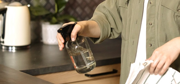 DIY kitchen cleaner and deodorizer in a brown glass spray bottle.