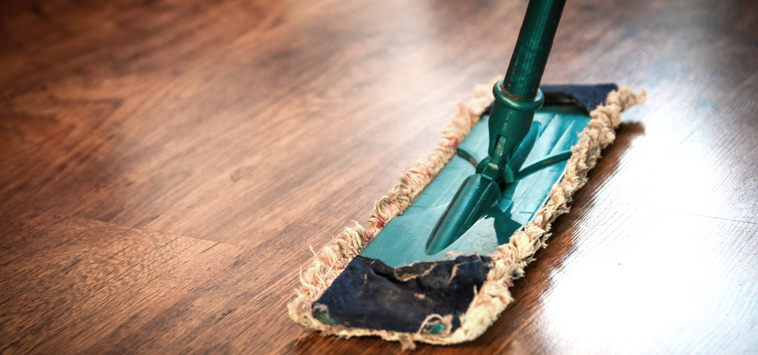 A mop head and soft towel ready to clean a wooden floor with DIY floor cleaner