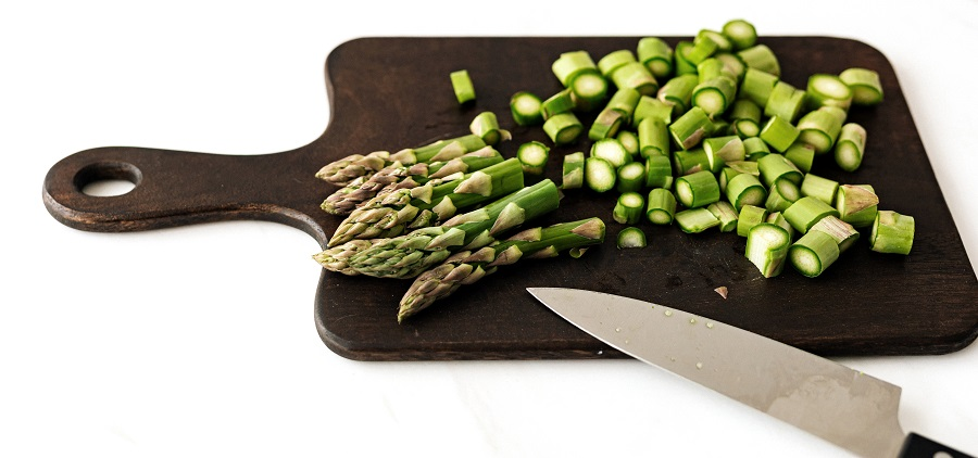 A brown wood composite cutting board with fresh cut asparagus on top