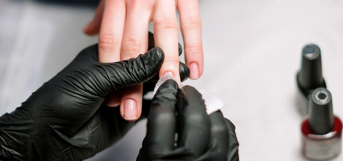 A salon worker removes a customer's nail polish using nitrile gloves